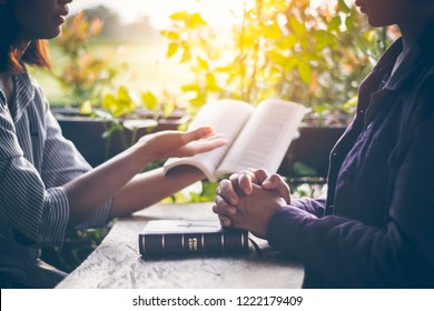 Asian girls are reading the sacred scriptures by pointing to the text of the book. And share the gospel and to explain the meaning of the Bible to her friend understand. Amid the meadows and greenery.