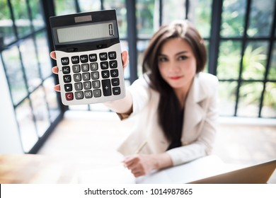 Asian girls show calculator Asian female accountant or banker perform calculations. Financial Savings and Economic Concepts