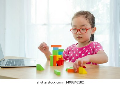 Asian girls wear pink shirts and red eyeglasses.Notebook computer on the wooden table in the room.Do not focus on objects.