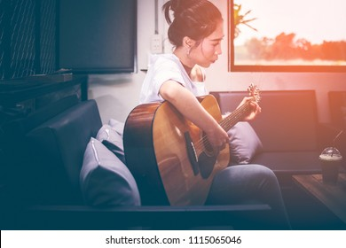 Asian girls wearing white shirts and jeans. She is sitting on a black couch is currently vacationing by playing guitar in a coffee shop. Iced coffee is placed on a wooden table.
