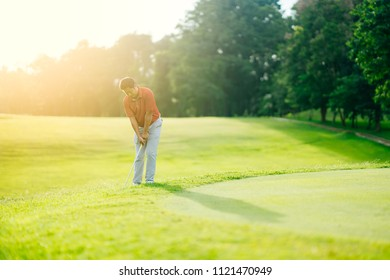 Asian golfer chip golf ball to winner in beautiful golf course on bright sunlight sunset. Player standing in rough grass for prepare chip shot. This sport is popular for people for exercise activity.