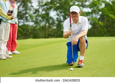 Asian golfer crouching and aiming before putting on green