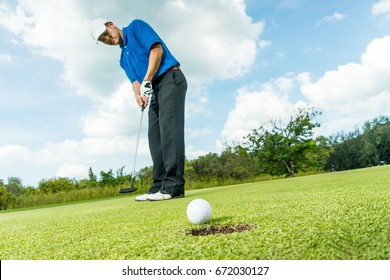 Asian golfer long putting golf ball straight to rim hole, copy space on Right side.