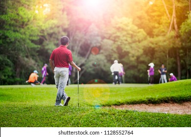 Asian golfer standing relax before play golf ball. It beautiful golf course on mountain. Player happy and playful for this shot. This sport is exercise and hobby for lifestyle business man