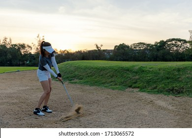 Asian Golfer woman playing golf and hitting out of a sand trap. People with the golf course is on the sand.  Hobby in holiday and vacations on club golf. Lifestyle and Sport Concept