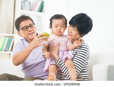 asian grand parents comforting their spoilt crying grand daugther