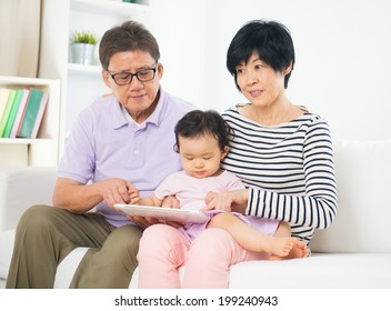 asian grand parents teaching grand son internet with a tablet