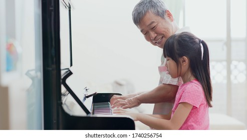 asian grandfather teach girl playing the piano happily
