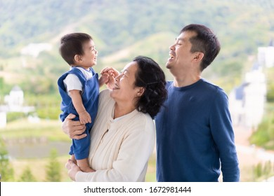 Asian grandmother is holding the little baby boy grandson and the boy laughing with father. Multi generation people in asian family lifestyle, love, relation, bonding, attachment, and elderly concept.