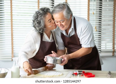 Asian Grandmother kissing Grandfather while their baking cookies at the house. Romantic, couple in love.