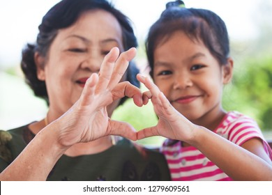 Asian grandmother and little child girl making heart shape with hands together with love