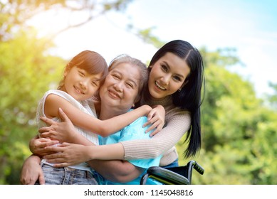 Asian Grandmother, Mother And Daughter Relaxing In Park.Insurance Concept