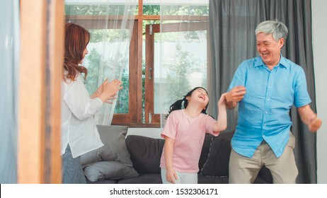 Asian grandparents and granddaughter listen to music and dance together at home. Senior Chinese, grandpa and grandma happy spend family time relax with young girl in living room concept.
