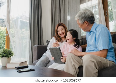 Asian grandparents and granddaughter using tablet at home. Senior Chinese, grandpa and grandma happy spend family time relax with young girl checking social media, lying on sofa in living room concept