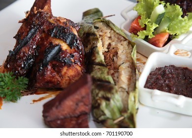 Asian grilled rice food in banana leaf with chicken an tofu on restaurant table