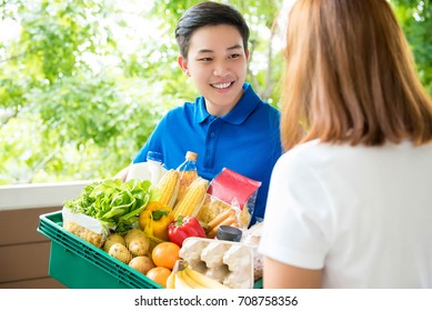 An Asian grocery store delivery man wearing a blue poloshirt delivering food to a woman at home