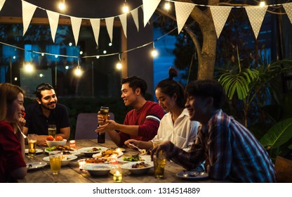 Asian group eating and drinking cold beer outside the house at night, having fun talking