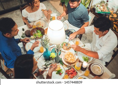 Asian group  friends eating dinner at home, they are happy to talk.