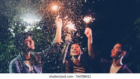 Asian group of friends having outdoor garden barbecue laughing with alcoholic beer drinks and showing group of friends having fun with sparklers on night ,soft focus