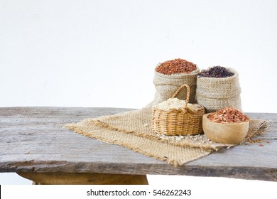 Asian group of grain rice. riceberry in gunny bag on old wooden isolate on white background