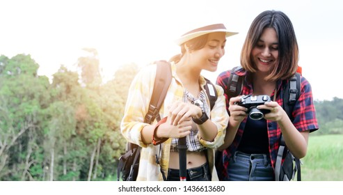 Asian Group of young people Hiking with friends backpacks walking together and looking map and taking photo camera by the road and looking happy ,Relax time on holiday concept travel