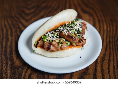 Asian gua bao with grilled chicken, teriyaki sauce, green onion and sesame seeds. Selective focus, small depth of field.