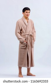 Asian guy in a bathrobe. A Kazakh man in a dressing gown on a light background.