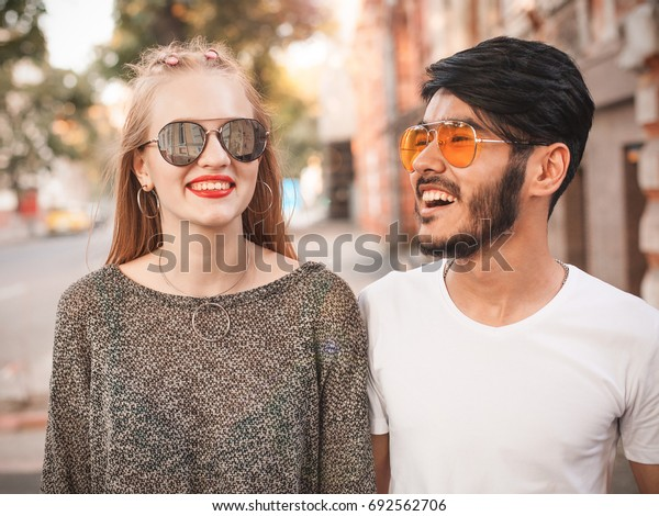 Asian guy and female are walking along the street.