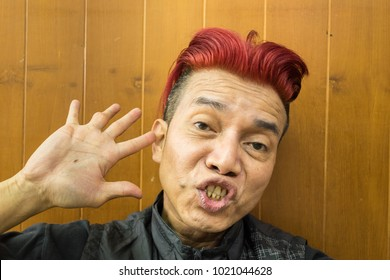 Asian guy with red hairs looking at the camera.
