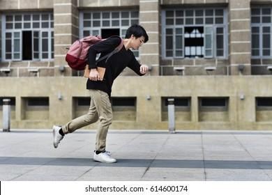 Asian Guy Running in a Hurry watching Time
