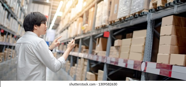 Asian guy shopper standing in warehouse inventory aisle checking shopping list on smartphone. Buying or purchasing factory goods. Shopaholic concept