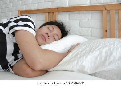 Asian guy sleeping in a white bedroom.Man sleeps well in bed in a white bedroom.