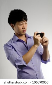 Asian guy take a photo with his smart phone