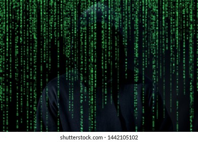 Asian hacker in black hood on black background with matrix foreground,Hack password,hacking safety systems to steal information