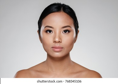 Asian half-naked beautiful lady without make-up looking camera isolated over grey