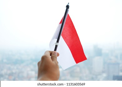 asian hand hold indonesian flag with white blur background. 17th august 1945. independence day of indonesia