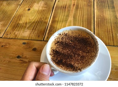 Asian hand holding a cup of cofee sprinkled with chocolate powder