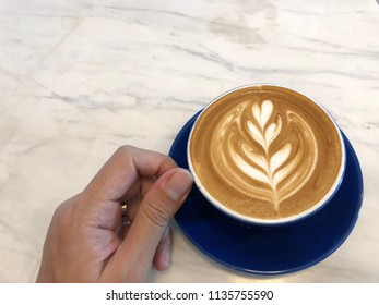 Asian hand holding a cup of Latte