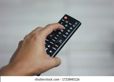 Asian hand holding television remote control and press button to switch channel. Concept for technology and rest time at home.