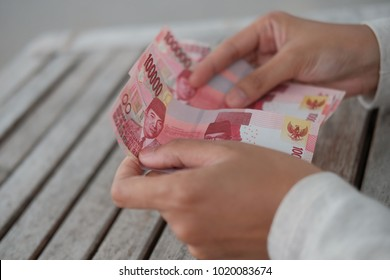 asian hand showing rupiah Indonesia money on top wood table