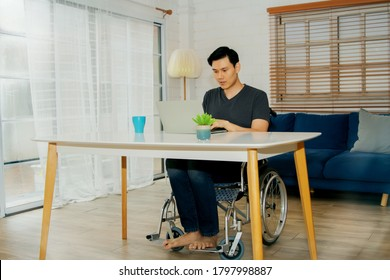 Asian handicapped man in a wheelchair uses his abilities to efficiently work on a laptop computer on a table in the home, despite the fact that his body is sick and ill with paralysis.