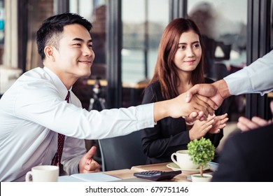 Asian handshake with new partner in office room, success business concept.
