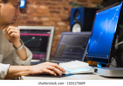 asian handsome business man working on multiple computer