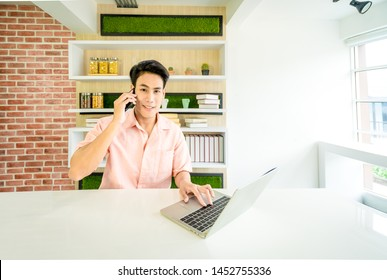 A Asian Handsome businessman 24s used mobile phone and working with laptop on desk in workplace near window,A handsome 24 year old Asian male student used phone and a laptop on the table in the house.