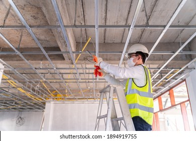Asian handsome electrician wearing a mask installing laying electrical cables on the ceiling with pliers inside the house under construction.