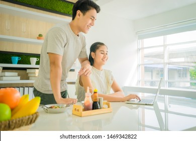 Asian Handsome man 24 years old smile and stand beside with Asian beautiful woman 24 years old smile, sitting both used laptop search for cooking methods on table in home in the morning near window