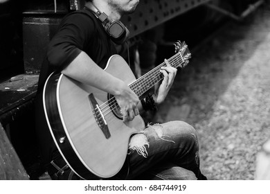 Asian handsome man musician playing the guitar,Focus hand on the cord,Black and white.