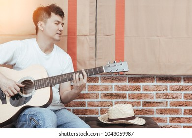 asian handsome man playing acoustic guitar on stool in loft design living room