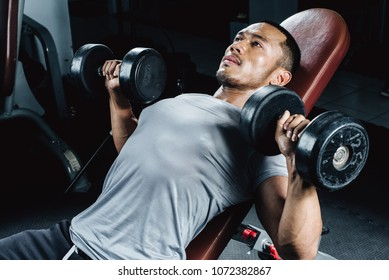 Asian handsome man posting with dumbbells in dark gym