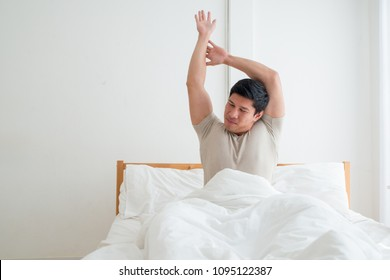 Asian handsome man waking up in the early morning. Outstretched arms. People always stretch after they get up in the morning